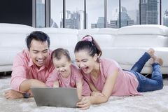Young family watching a movie on a laptop. Picture of young family watching a movie on the laptop while laughing together on the carpet Royalty Free Stock Images