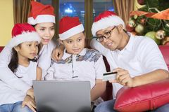 Young family shopping online at Christmas time stock photography
