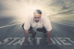 Young fat man kneeling above text of start diet stock photo