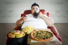 Young fat man enjoying junk foods on the sofa. Picture of a young fat man watching television while enjoying junk foods and cola on the sofa. Shot at home royalty free stock photography