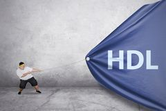 Young fat man pulls HDL word in the banner stock photography