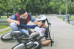 Young father helps his son after falls from a bike stock photo