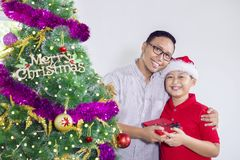 Young father giving gift box for his son. Picture of a young father smiling at the camera while giving a gift box for his son near a Christmas tree Royalty Free Stock Photo