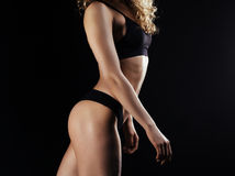Picture of young female athlete back on dark background. Fitness model posing in studio Royalty Free Stock Images