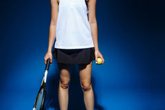 Picture of young fintess girl holding tennis racket and ball in studio Stock Images