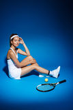 Picture of young fintess girl near tennis racket and sitting on floor in studio Royalty Free Stock Image