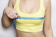 A picture of a young fit happy woman checking her breast measurement over white background stock images