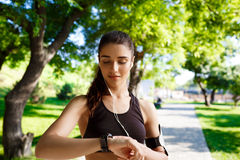 Picture of young  fitness girl looking on watch. Nature background Stock Photography