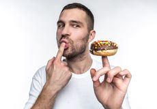 A picture of young guy that want to calm his hunger He decided to eat tasty but oily chocolate donut that he has on his. Finger. He can`t wait to eat it Royalty Free Stock Photography