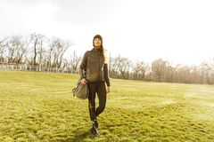 Picture of young handicapped girl with prosthetic leg in sportswear, walking on grass in sunny day royalty free stock images