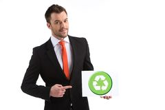 Picture of young happy man on white background. Smiling guy pointing to recycle sign stock photo