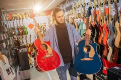 Picture of young hipster stand and hold two colorful acoustic guitars. They are red and dark-blue colors. Guy look at. Second one. Man electric guitars are stock photos