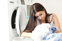 Portrait of young housewife with laundry next to washing machine Royalty Free Stock Photography