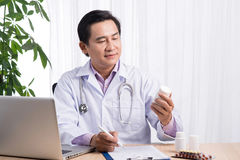 Picture of young male asian  doctor with jar of capsules in his Royalty Free Stock Images