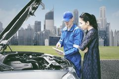 Mechanic talking with his client in the roadside. Picture of young male mechanic using a tablet to checking broken car while talking with his client in the Royalty Free Stock Images