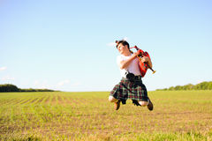 Picture of young man jumping high with pipes in Royalty Free Stock Image