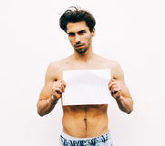 Picture of young man with naked torso holding white blank board. Outdoor Royalty Free Stock Images