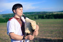 Picture of young man playing pipes on green summer Royalty Free Stock Image