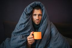 Picture of young man sits on bed and covered up with dark blue blanket. He holds orange cup of tea. Guy looks on camera. He is serious. Young man is stock photo