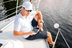 Picture of young man sits at edge of yacht board and hold tablet. It has dark screen. Man wears sunglasses and white cap. With shirt. He is serious and stock images