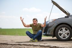 Picture of young man sitting next to broken car with open hood stock photography