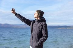 Picture of a young man taking a selfie with his phone royalty free stock photo