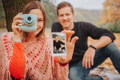 Picture of young man and woman look straight and smile. She holds blue camera and picture in hands. There are young man royalty free stock photography
