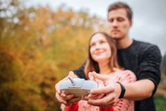 Picture of young man and woman standing together and holding remote control from drone. He is behind her. Woman looks up. royalty free stock photo