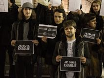 Young people holding `Je suis Charlie` signs during a demonstration to commemorate 7th of January attacks against Charlie Hebdo. Picture of young people at night royalty free stock images