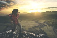 Young photographer takes a sunset photo. Picture of young photographer standing on the cliff while using a camera to take a sunset photo Stock Photography