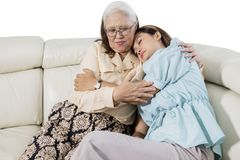 Sad woman embracing her mother on studio. Picture of young sad women embracing her mother while sitting on the couch, isolated on white background stock photos