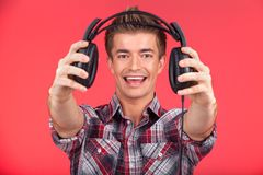 Picture of young smiling man offering headphones. Royalty Free Stock Images