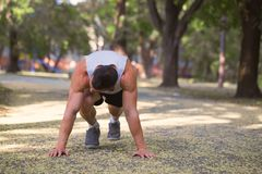 Picture of a young sportsman doing doing stretching exercise out. Doors, fitness and exercising in the park. Sport, recreation, lifestyle concept Stock Photo