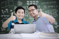 Young teacher and his student showing thumbs up. Picture of young teacher and his student showing thumbs up while using a laptop in the classroom Royalty Free Stock Images