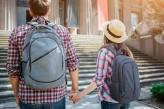 Picture of young tourists standing in front of stairs. They hold each other`s hands. Travellers wear rocksacks on their royalty free stock photo