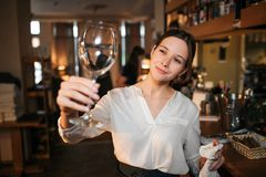 Picture of young waitress stand and look at clean glass for wine. She hold white towel in another hand. Waitress work at stock image