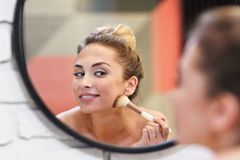 Young woman applying makeup with brush in bathroom stock image