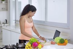 Young woman looking at recipes on a laptop royalty free stock image