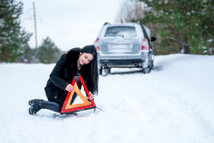A picture of a young woman having a problem with a car on a wint Stock Photography
