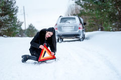A picture of a young woman having a problem with a car on a wint Royalty Free Stock Photos