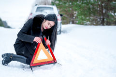A picture of a young woman having a problem with a car on a wint Stock Image