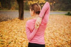 Picture of young woman stands in autumn park and look to left. She stretches hands. Woman keep them together behind back. stock images