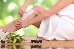 Young woman waxing her legs. A picture of a young woman waxing her legs Stock Image