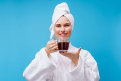 Picture of young woman in white coat and towel on her head with mug of coffee. On empty blue background stock photos