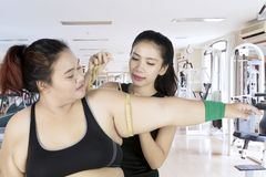 Young woman measuring bicep of fat woman. Picture of young women measuring bicep of fat women while standing in the fitness center Royalty Free Stock Photography