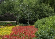 Wind sculptures in a colorful flower bed in the Dallas Arboretum and Botanical Garden. Pictured is an arrangement of three wind sculptures in a flower bed of Royalty Free Stock Image