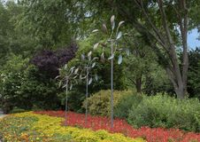 Wind sculptures in a colorful flower bed in the Dallas Arboretum and Botanical Garden. Pictured is an arrangement of three wind sculptures in a flower bed of Royalty Free Stock Photos