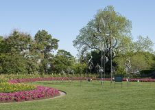Windsculptures and flower beds, Dallas Arboretum and Botanical Garden. Pictured is an arrangement of wind sculptures by Lyman Whitaker on grass surrounded by Stock Photos