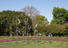 Windsculptures and flower beds, Dallas Arboretum and Botanical Garden. Pictured is an arrangement of wind sculptures by Lyman Whitaker on grass surrounded by Royalty Free Stock Images