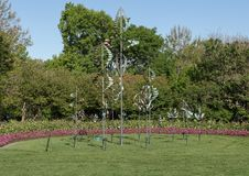 Windsculptures and flower beds, Dallas Arboretum and Botanical Garden. Pictured is an arrangement of wind sculptures by Lyman Whitaker on grass surrounded by Royalty Free Stock Photos
